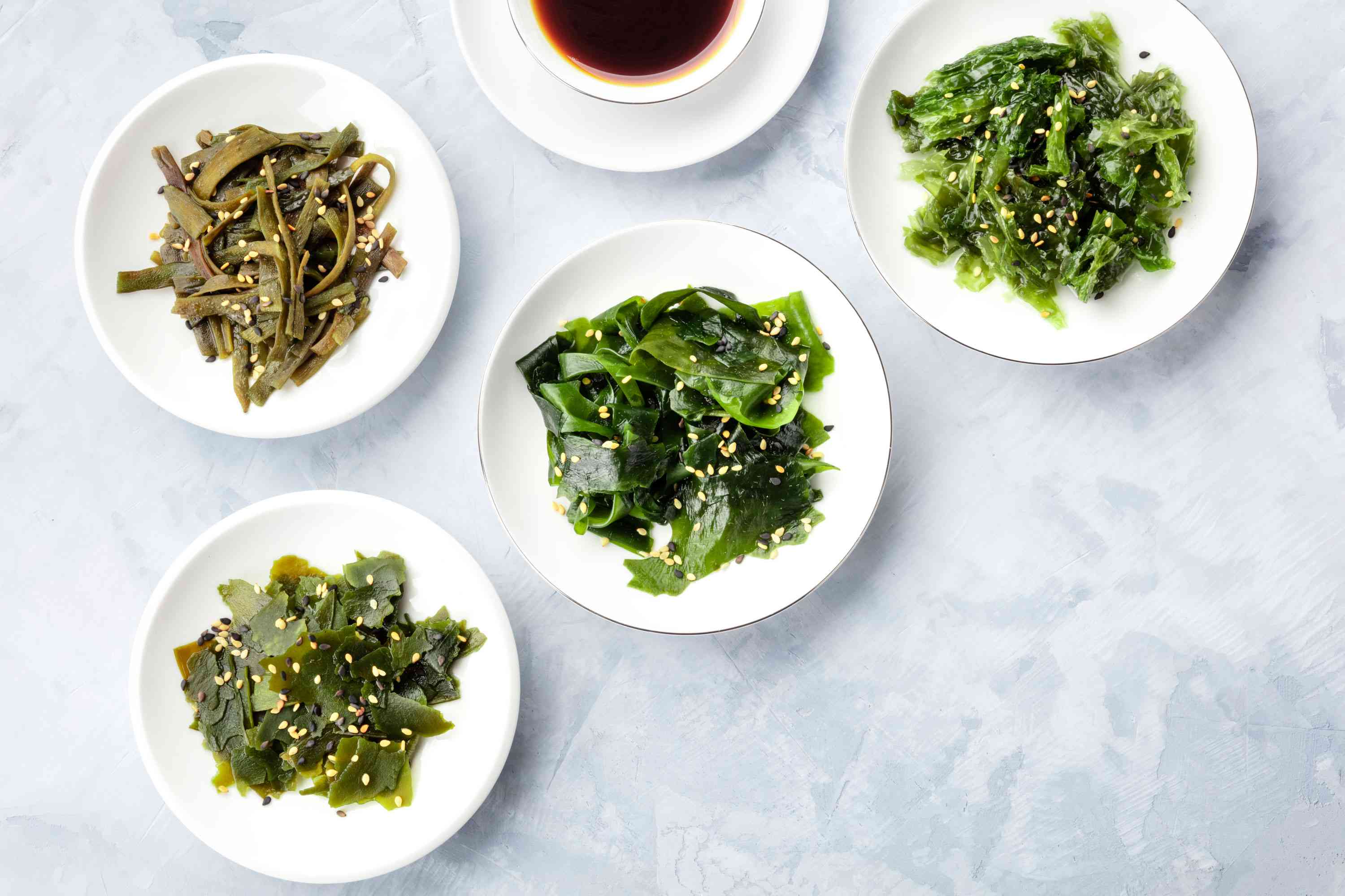 Bowls of different types of seaweed topped with sesame seeds
