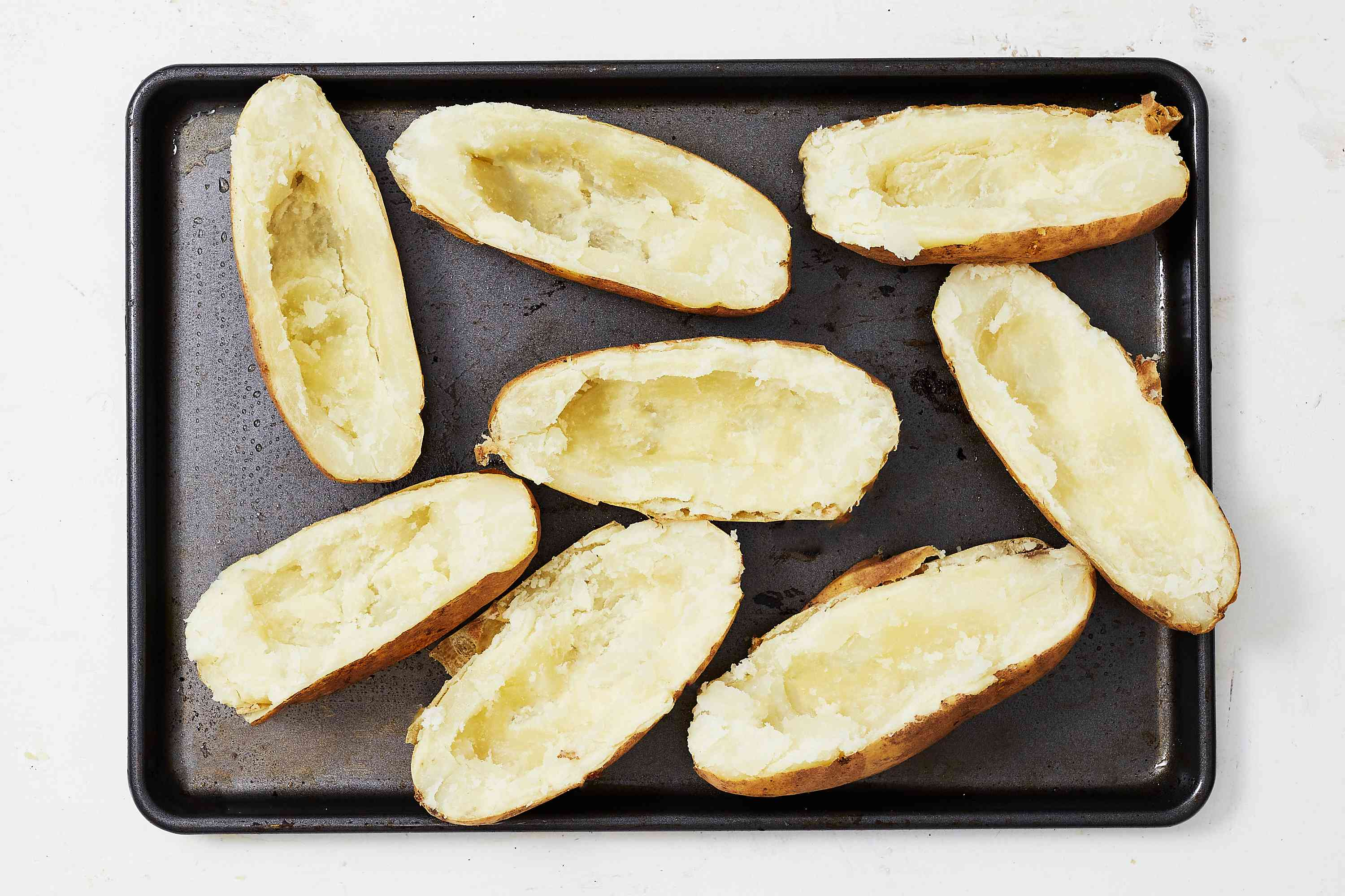Scoop out the potato, leaving the skins intact on a baking sheet