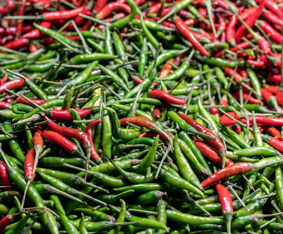 Asian bird's eye chili peppers mixed together on display at a market vendor