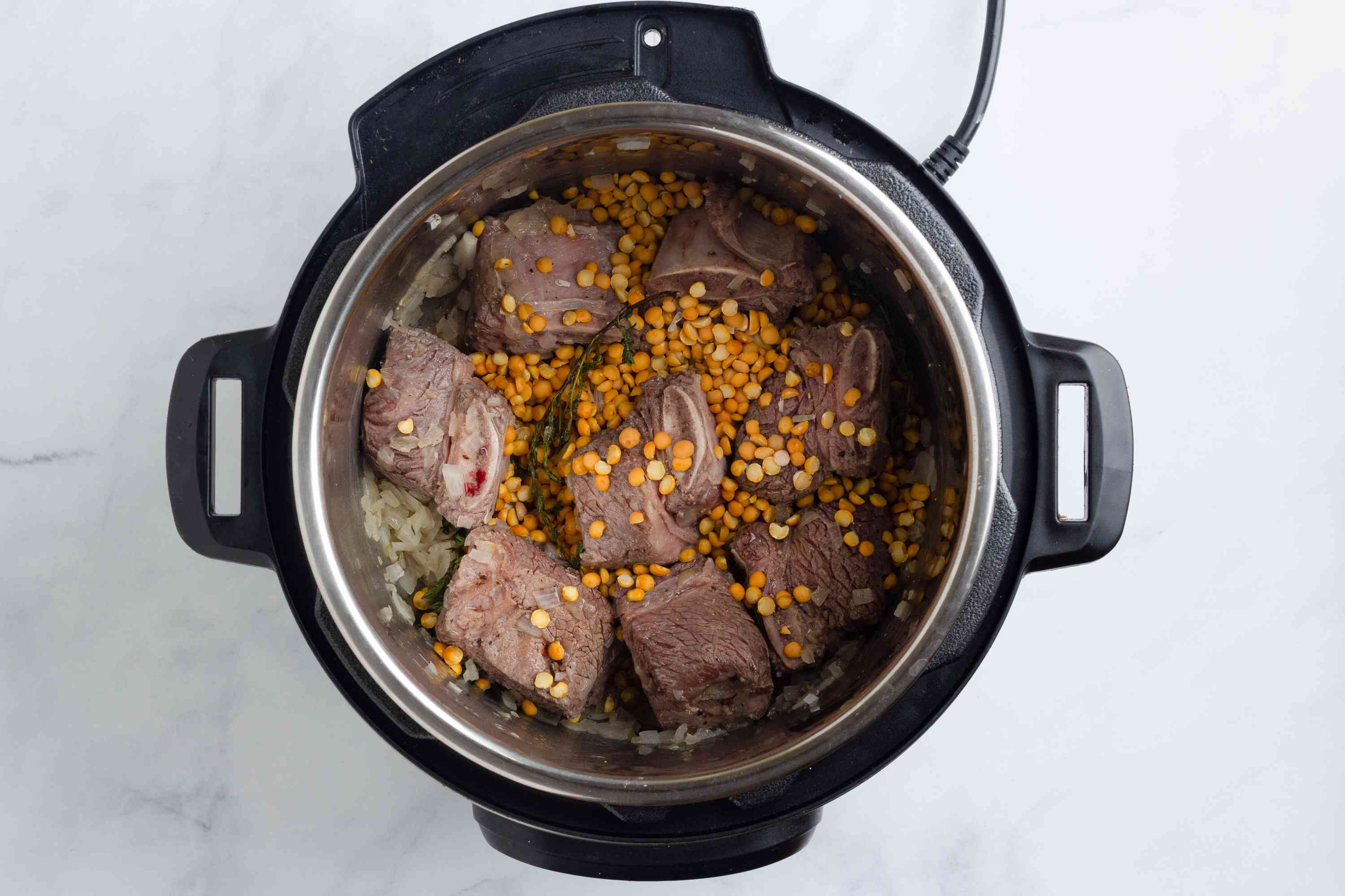 beef, with peas, onions and herbs in the pressure cooker