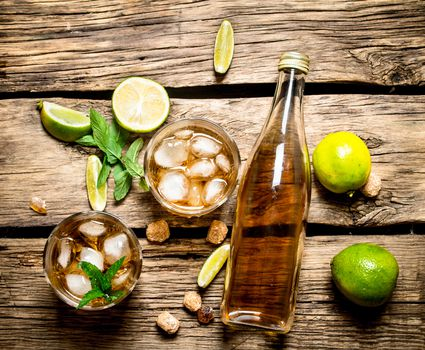 A bottle of rum, limes and mint