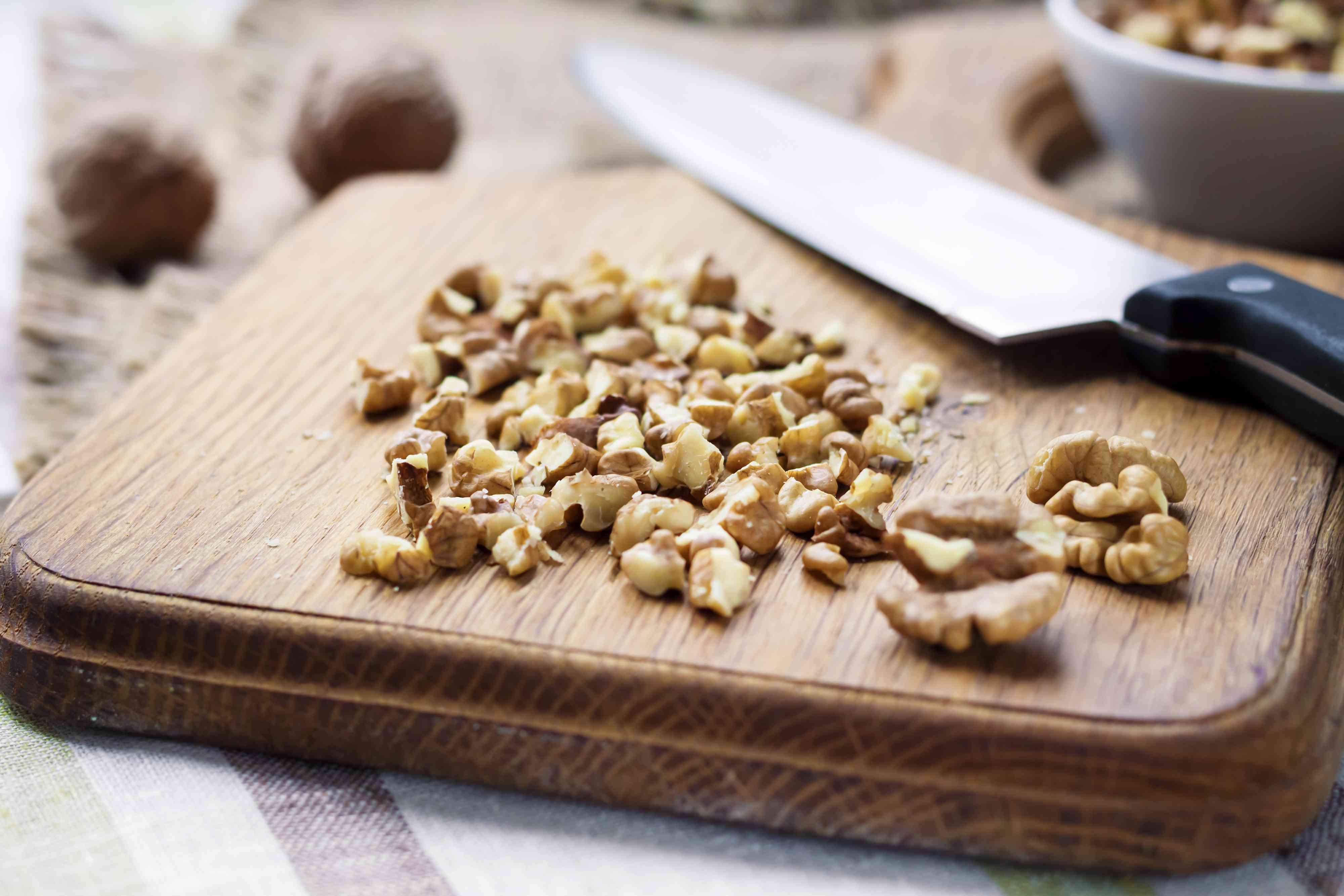 Chopped walnuts on wooden cutting board
