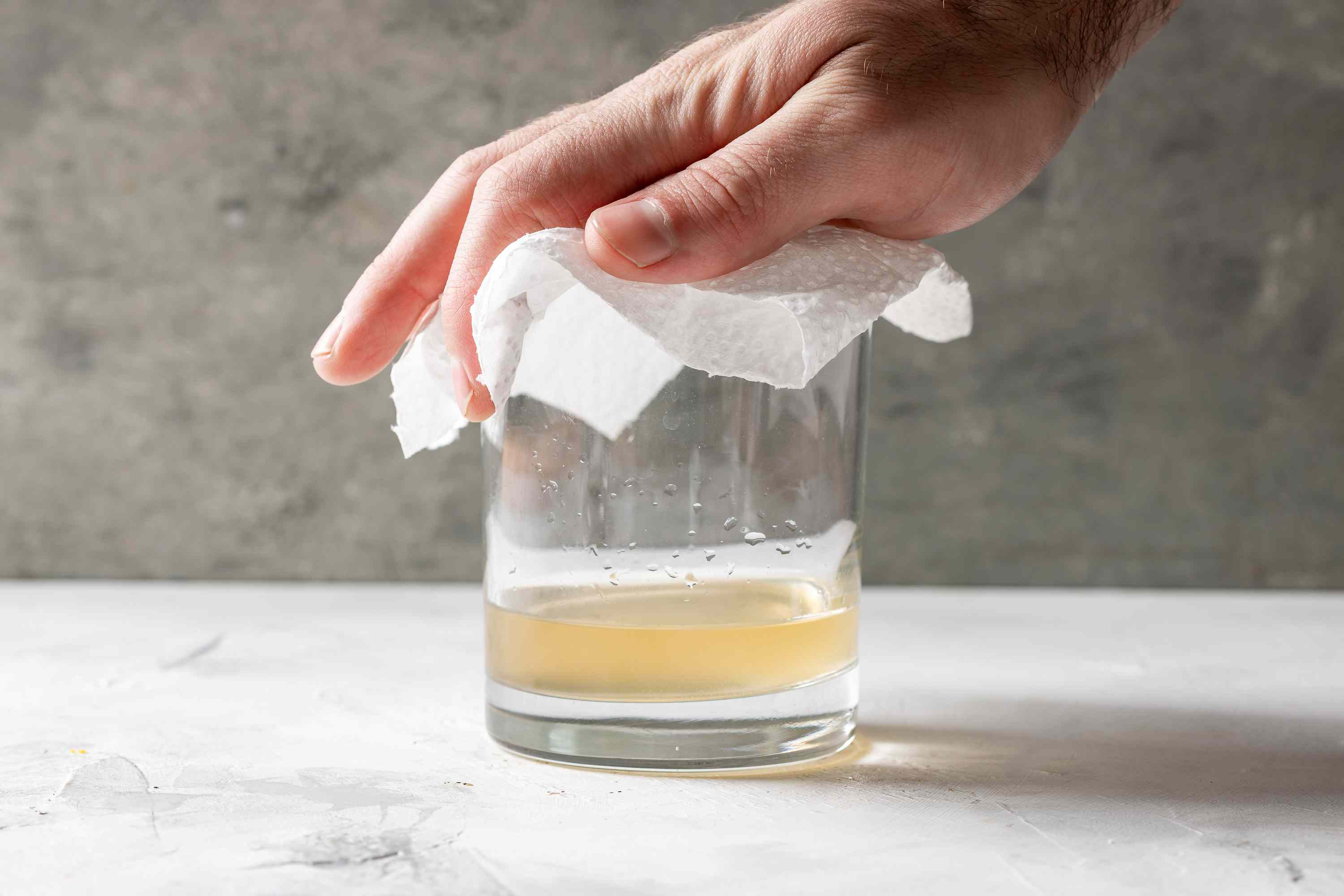 glass tequila and soda, hand holding napkin on top of glass