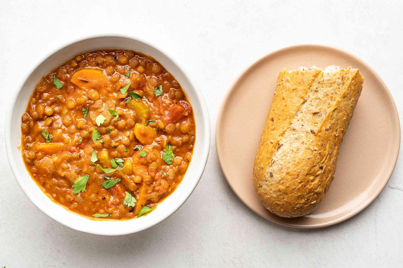 Instant Pot Lentil Soup in a bowl, bread on a plate