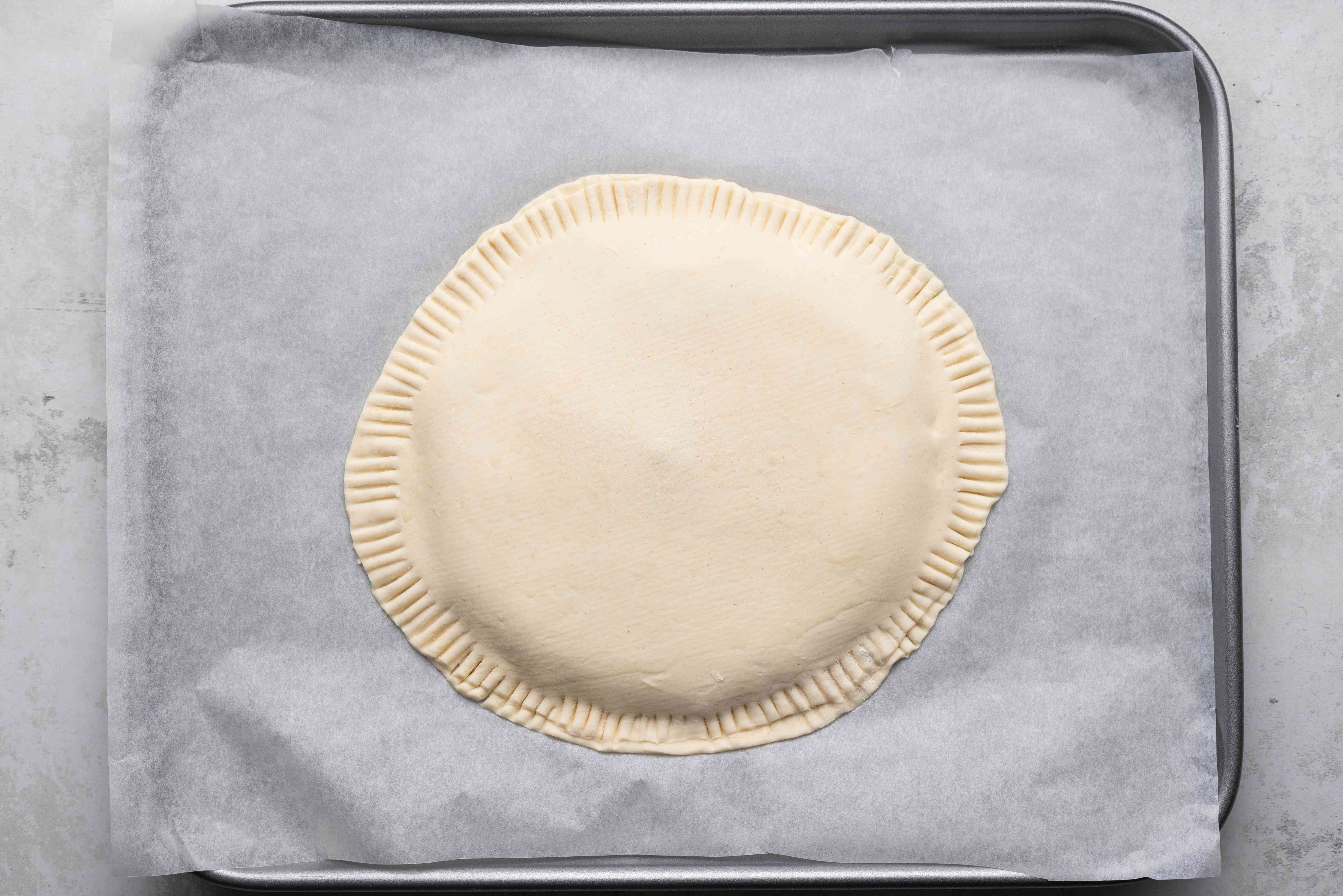 Place second puff pastry disc on top of filling, and crimp edges on a baking sheet