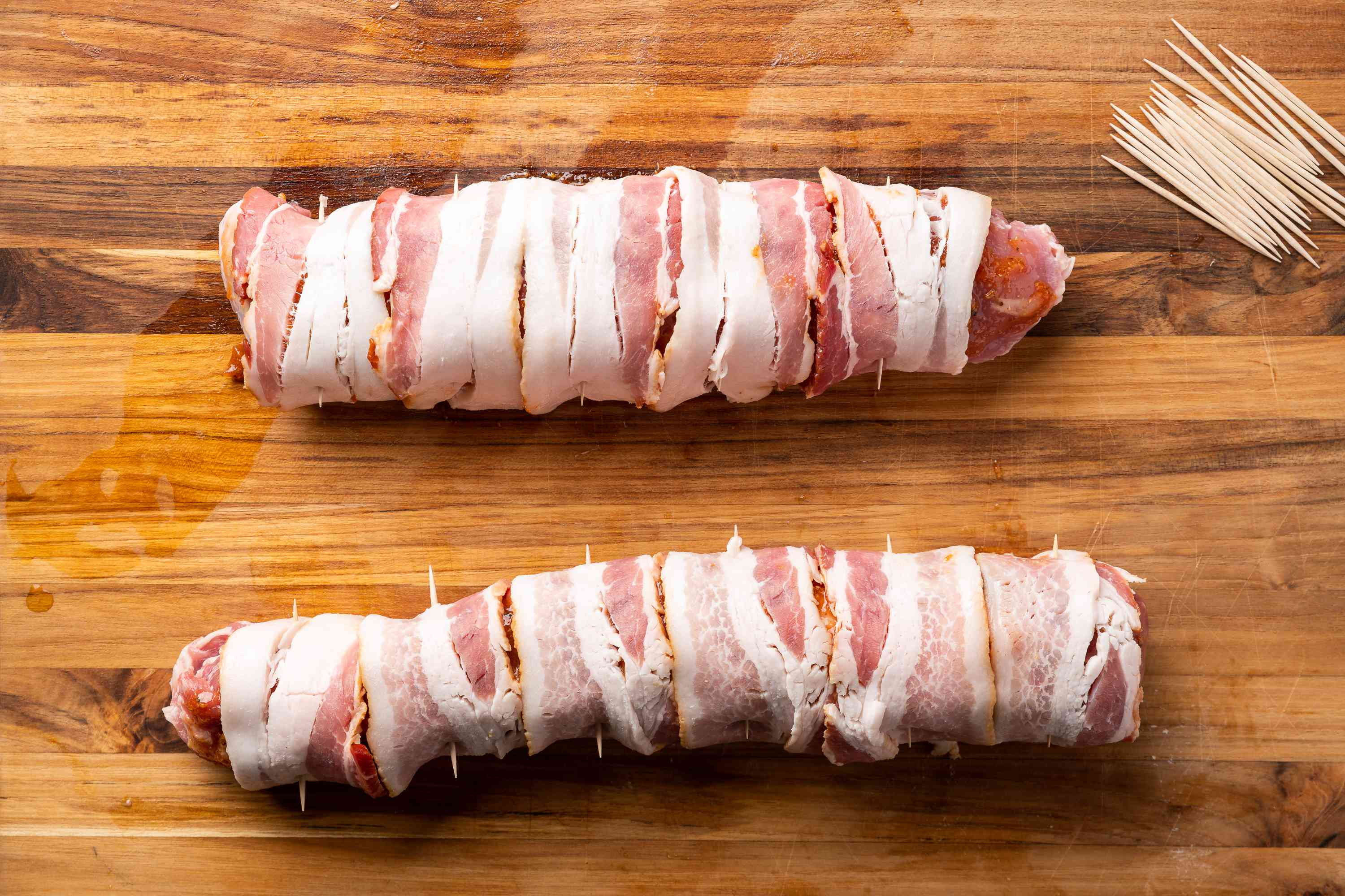 Cut bacon slices in half and wrap around the pork, secure with toothpicks