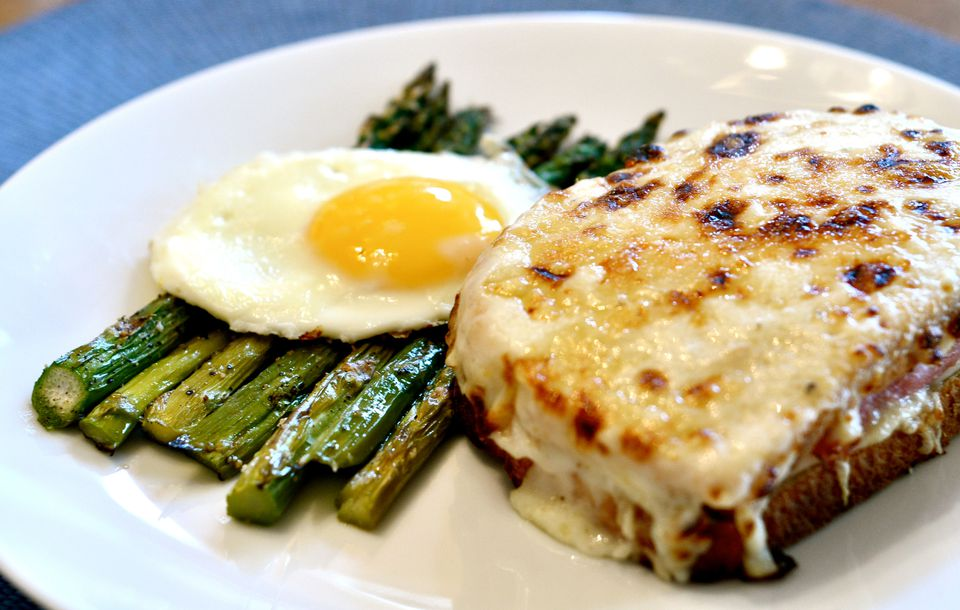 Croque monsieur sandwich on a plate with egg and asparagus