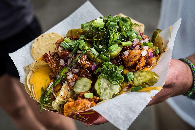 Hand holding loaded nachos