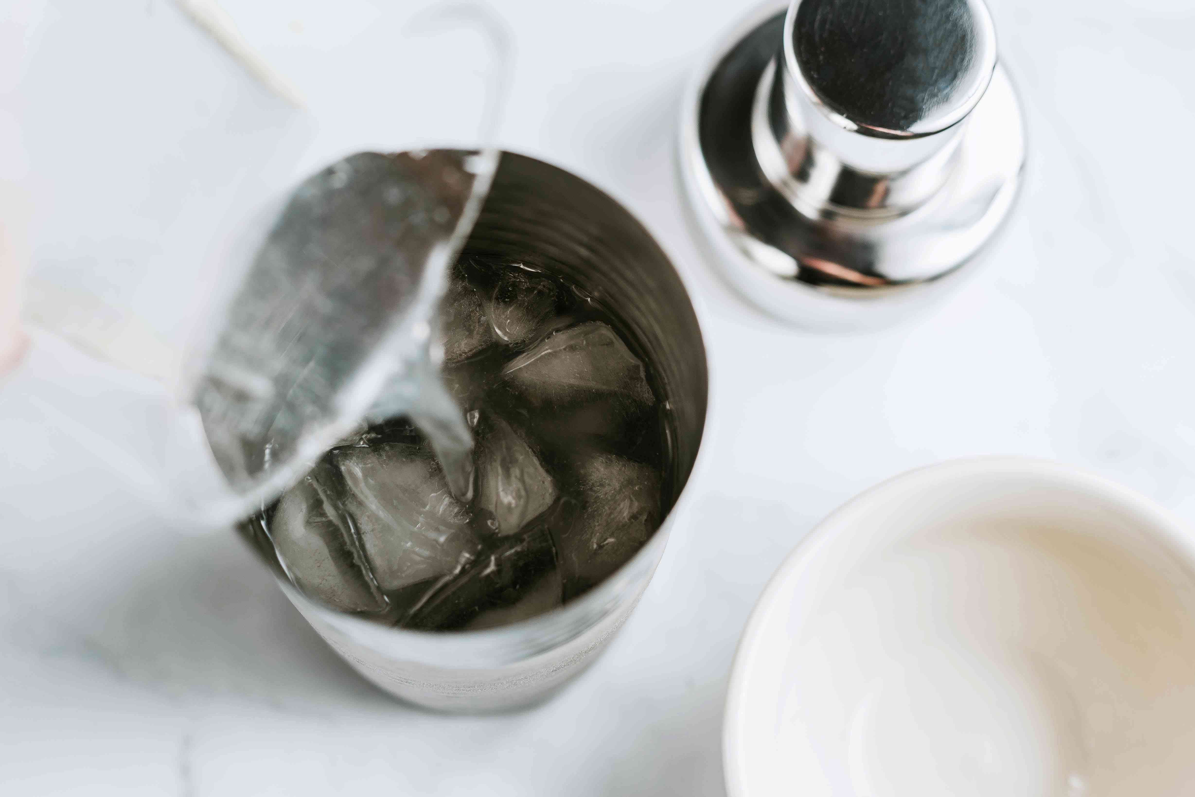 Cocktail shaker with ice cubes, vodka, lime juice, and triple sec