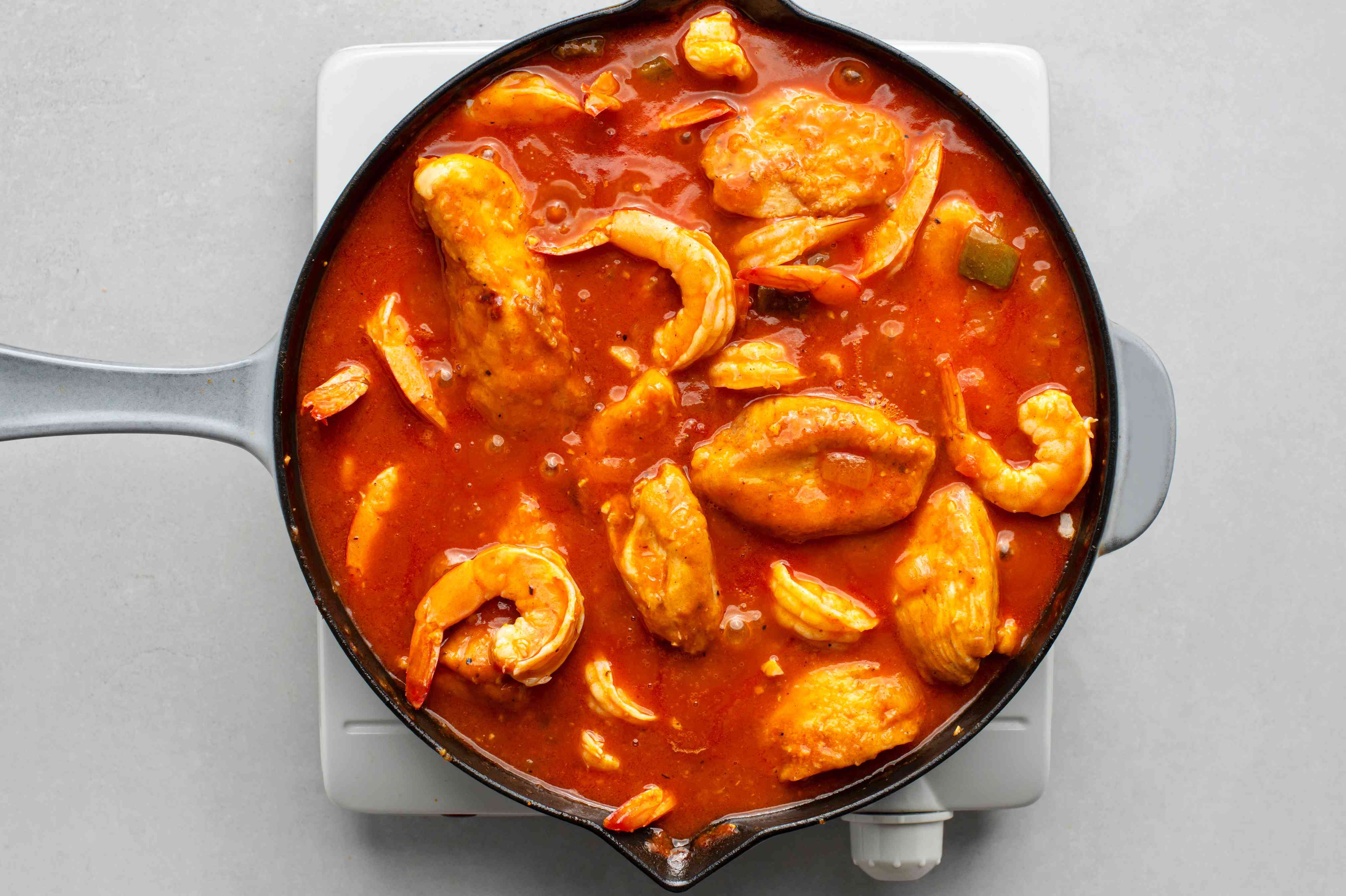 shrimp added to the chicken mixture in the skillet