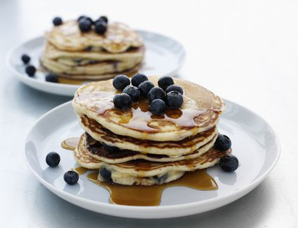 Two plates stacked high with blueberry pancakes