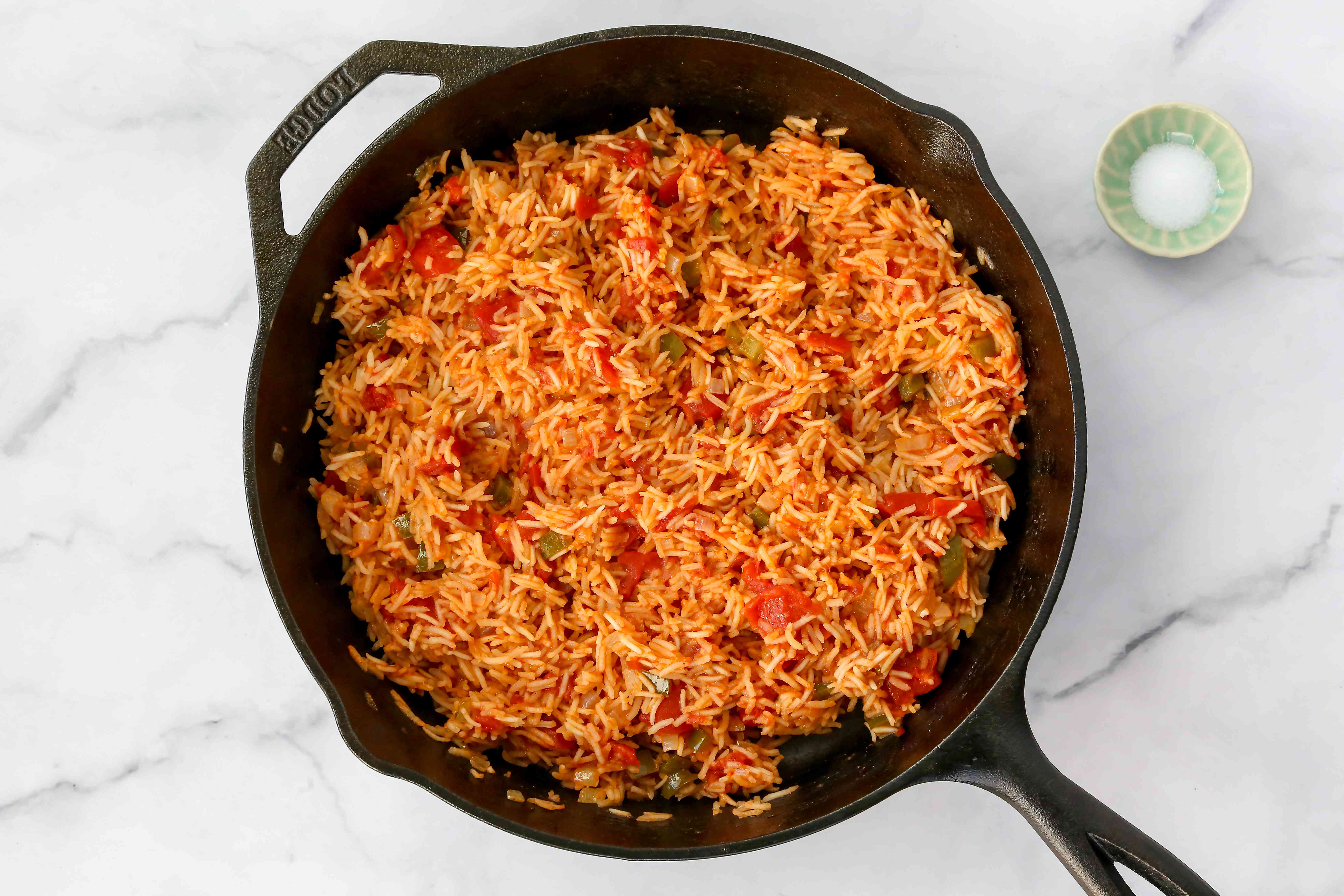 Mexican rice cooking in a cast iron skillet