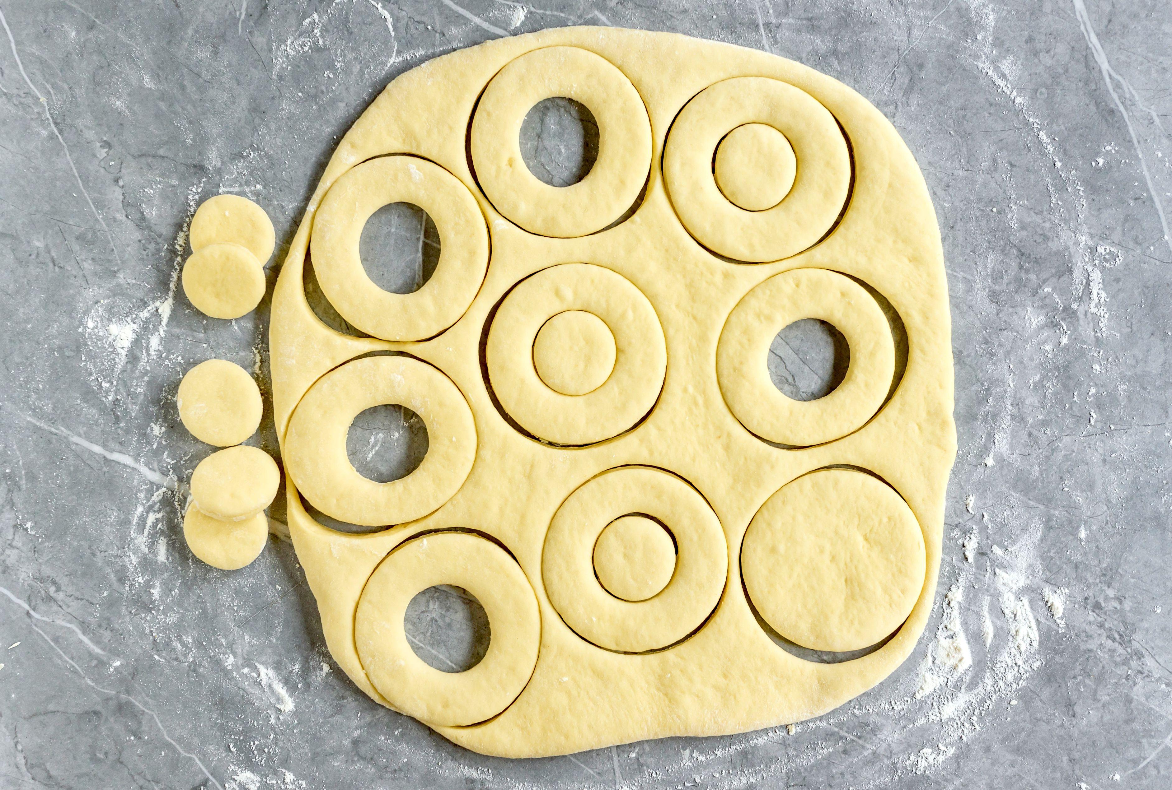 Doughnuts being cut from dough