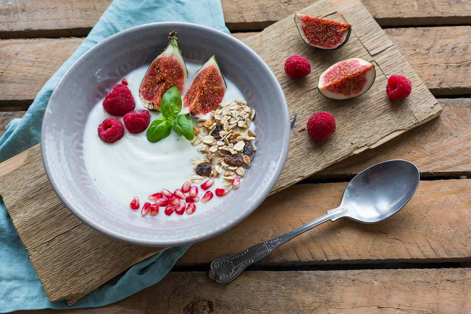 Bowl of natural yoghurt with fruit muesli, raspberries, figs and pomegranate seed