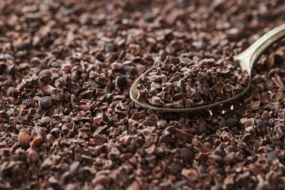 A silver spoon taking a scoop of cacao nibs