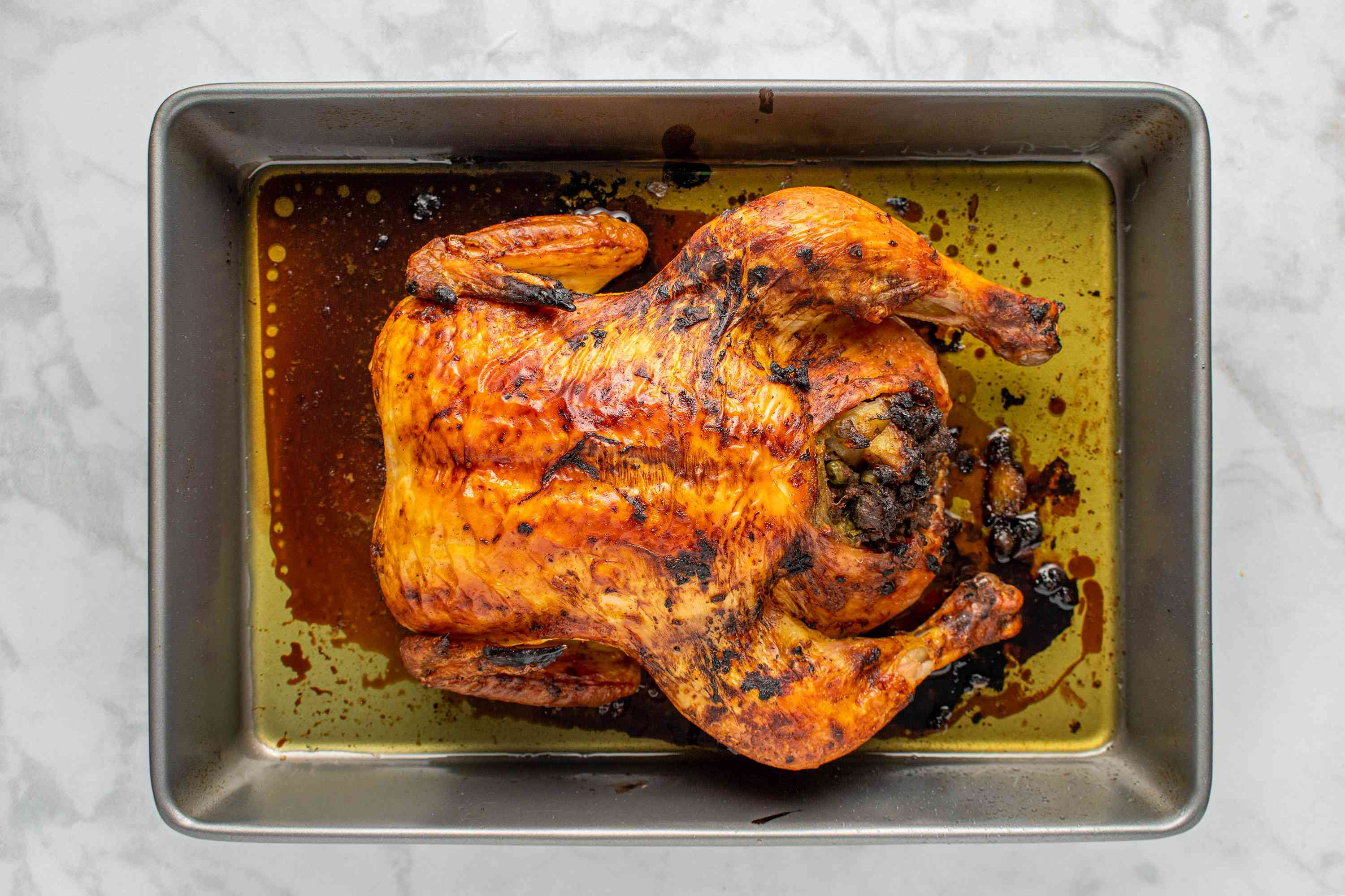 Indian-Style Stuffed Roast Chicken in a baking dish