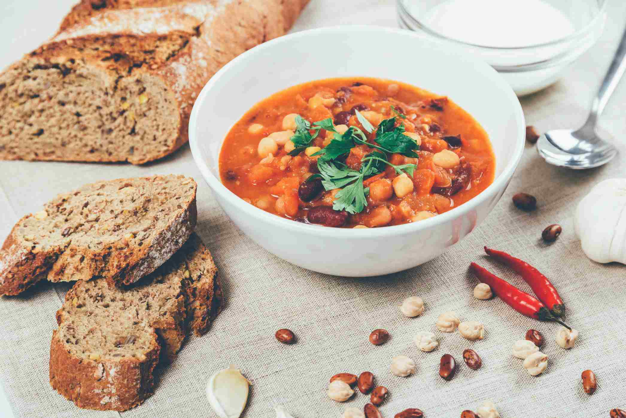 Vegetarian bean cholent with parsley garnish plus a loaf of bread