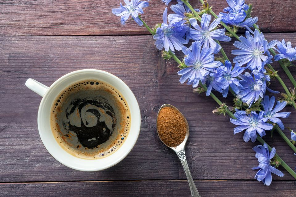 Chicory in a mug next to spoon and flowers
