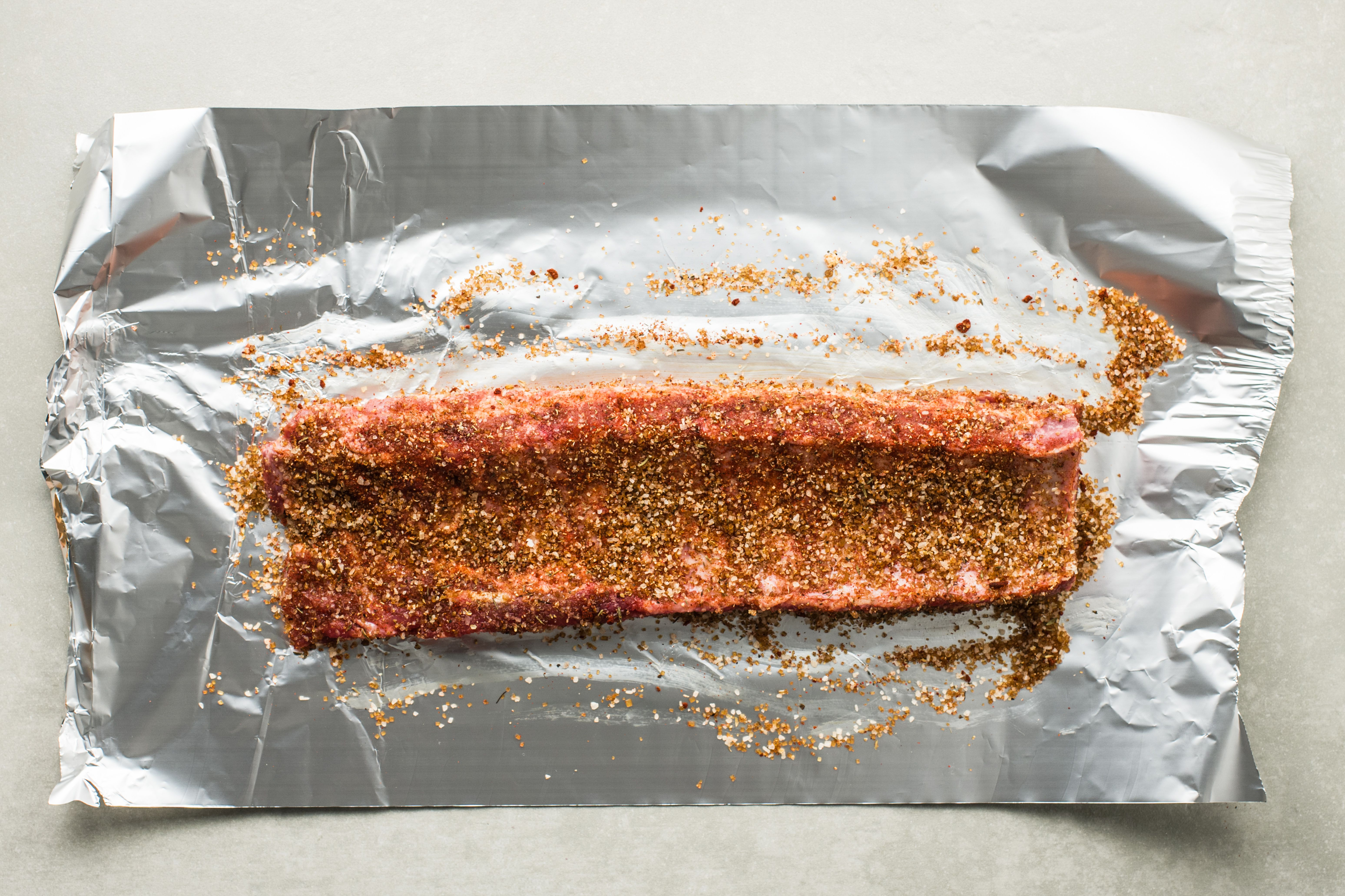 Rib rack covered in spices on a piece of aluminum foil