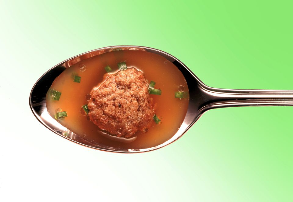 Meatball in broth on a silver spoon
