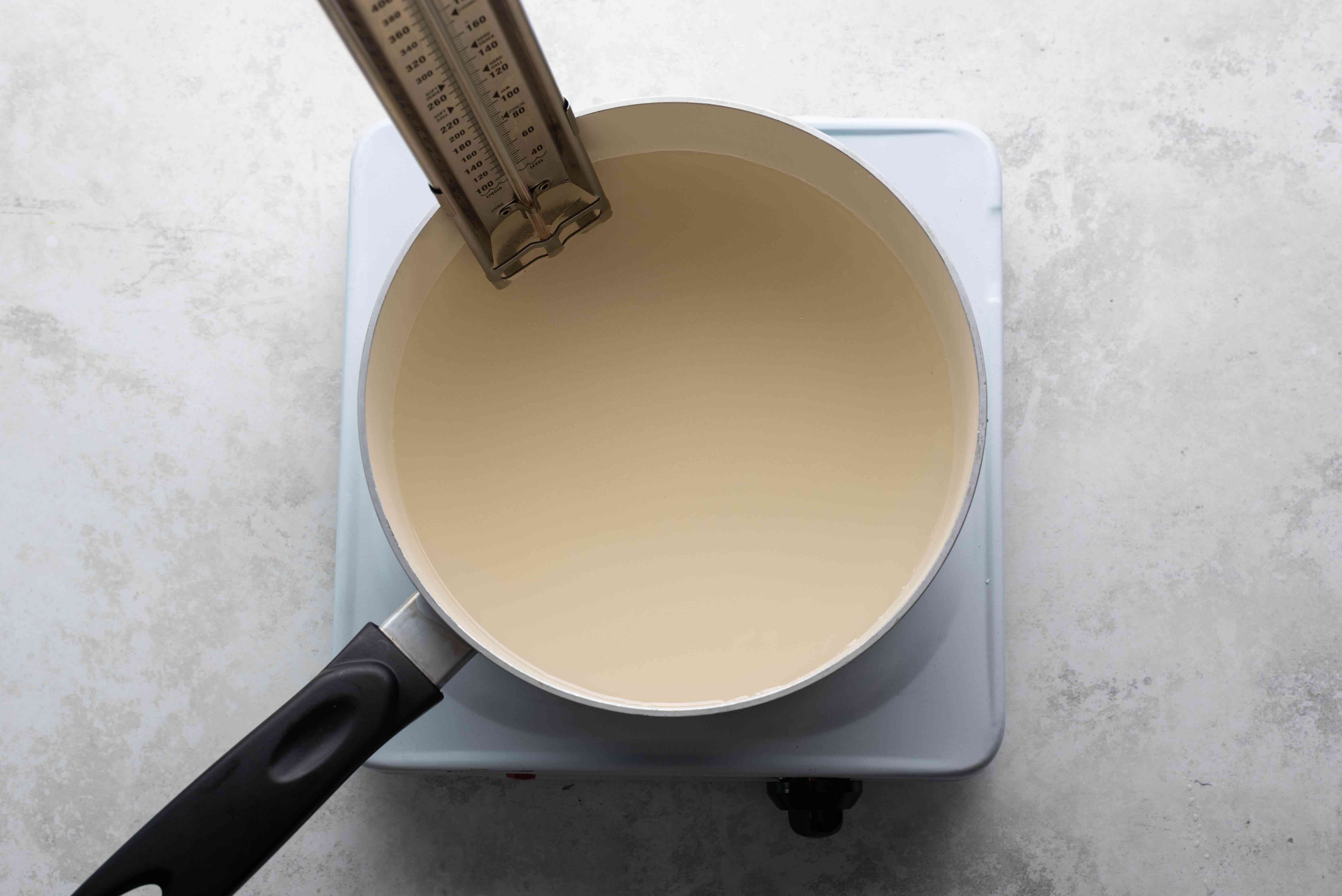 sugar thermometer in a saucepan with the syrup