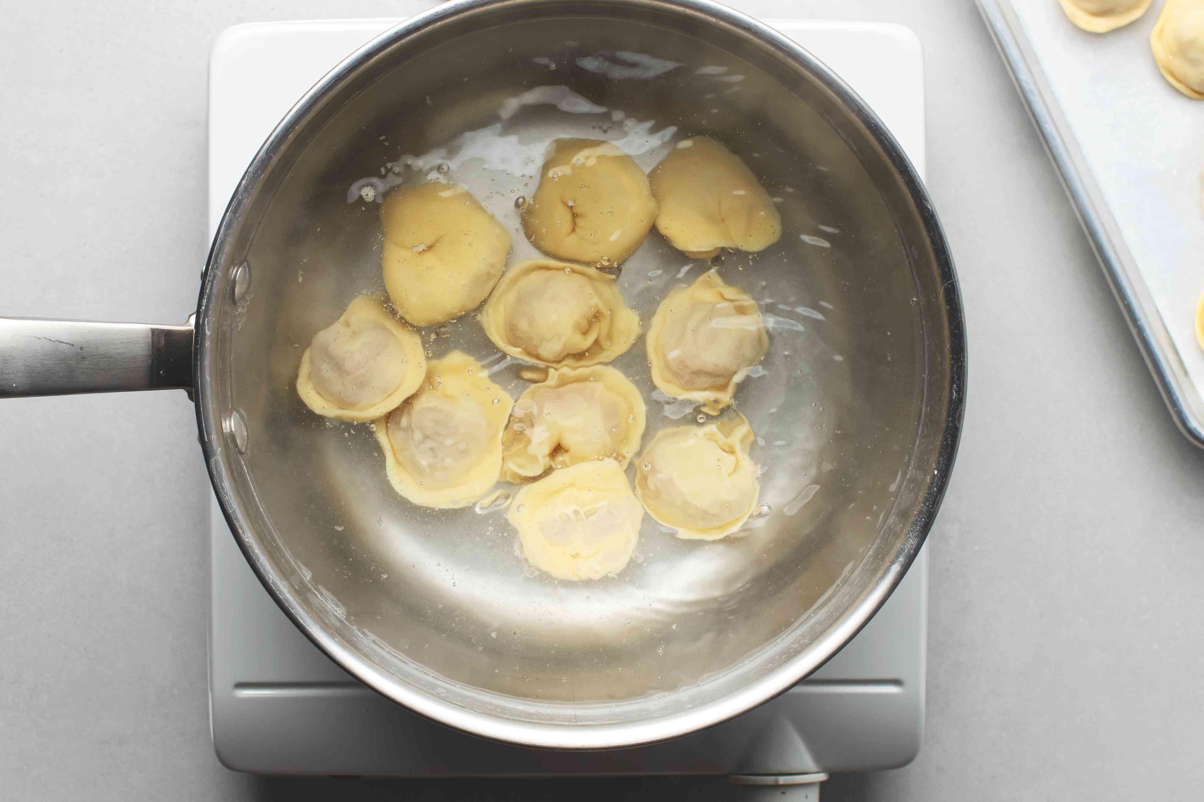 pelmeni cooking in pot of water