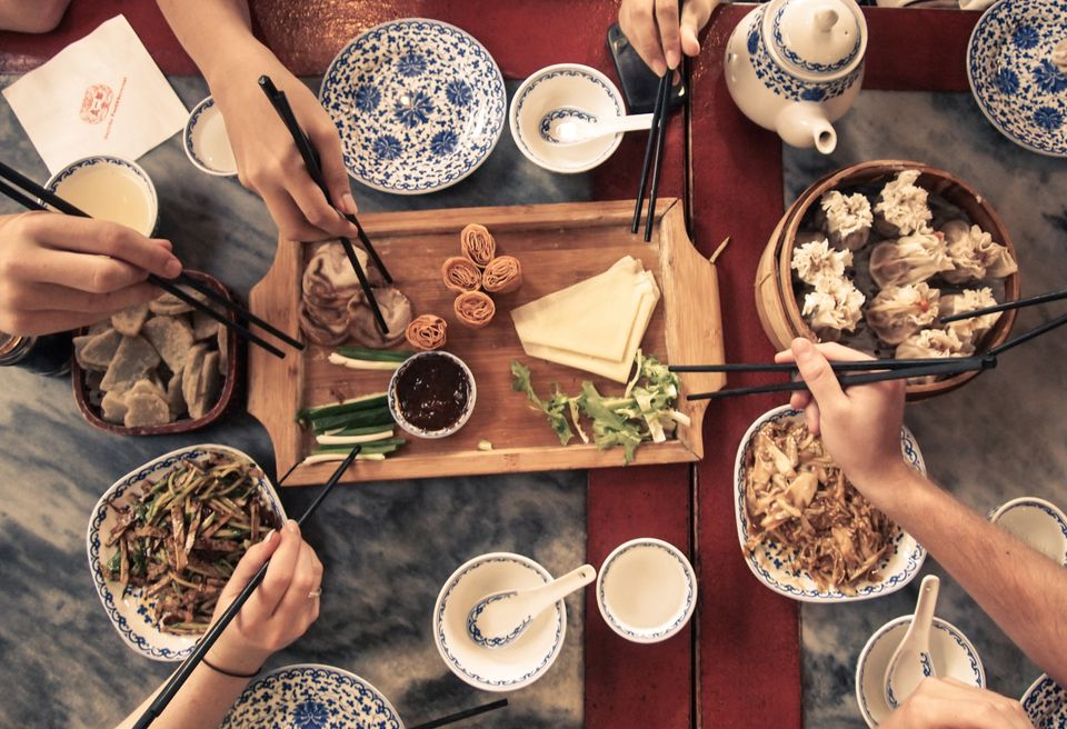Several hands using chopsticks to pick up shared food