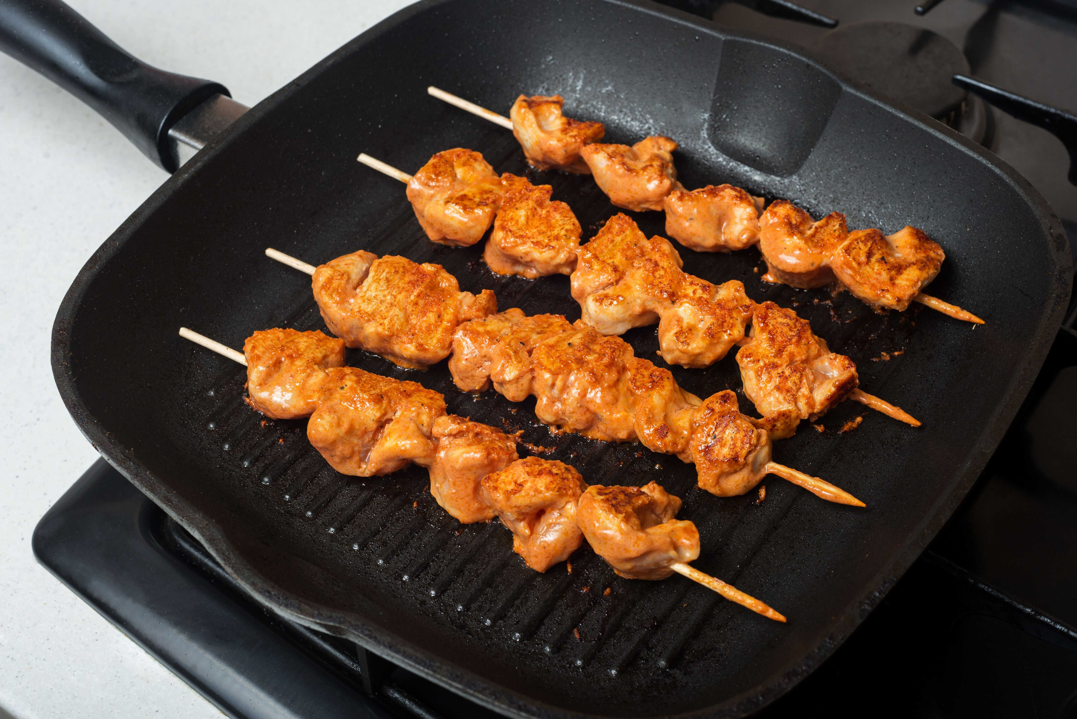 Turkish chicken kebabs cooking in a grill pan