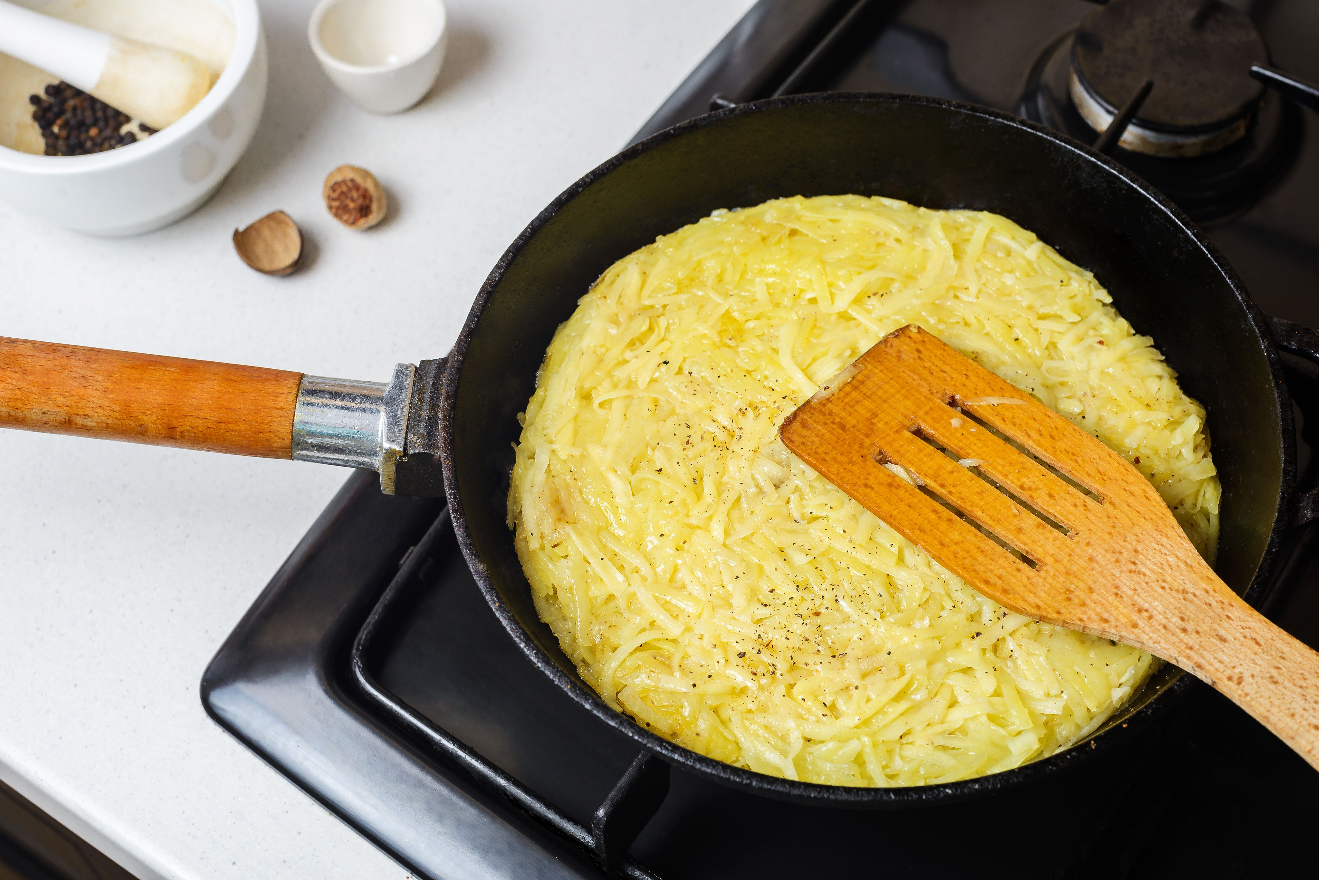 Grated potatoes frying in a skillet