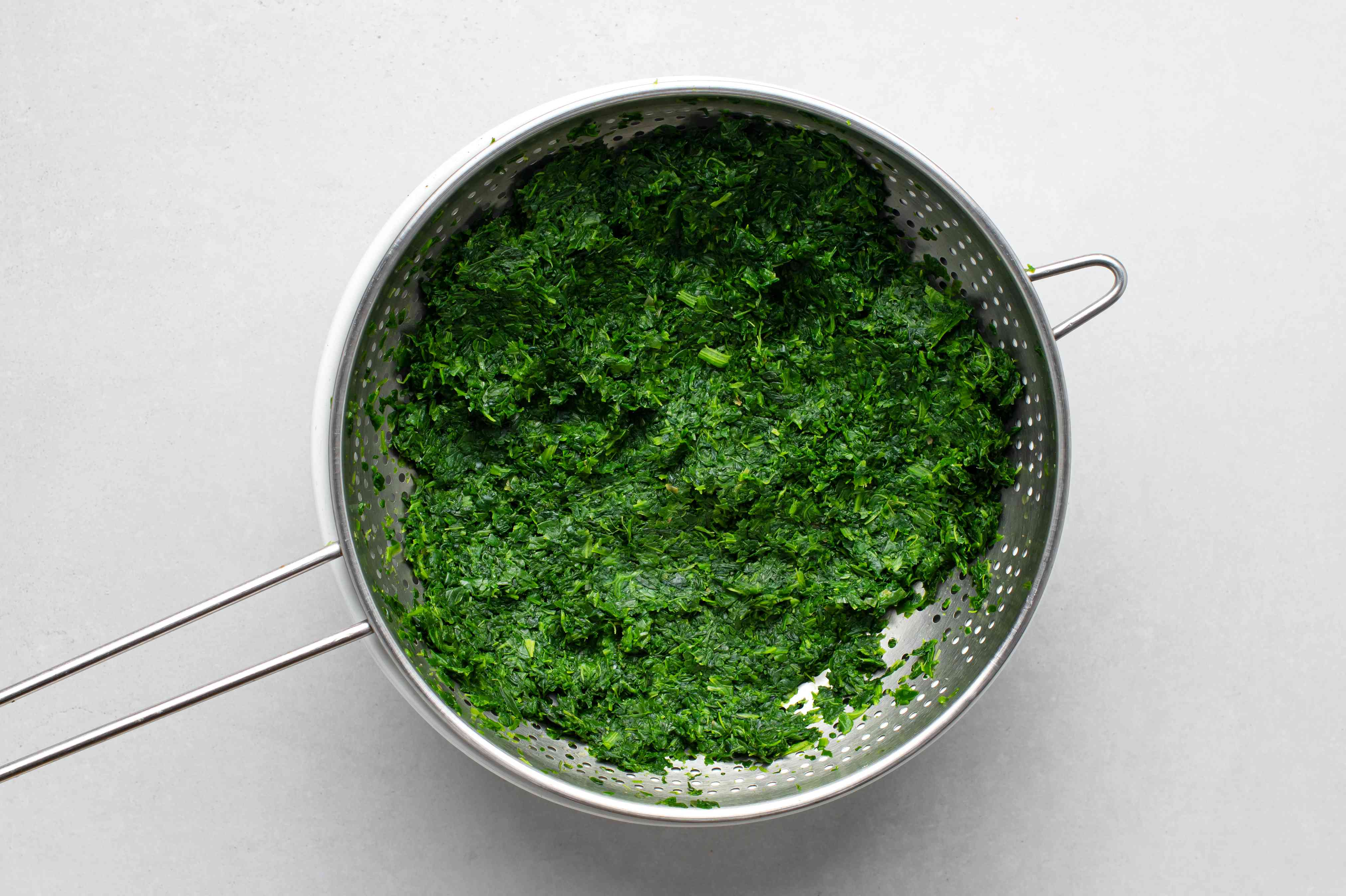 drained cooked spinach in a colander