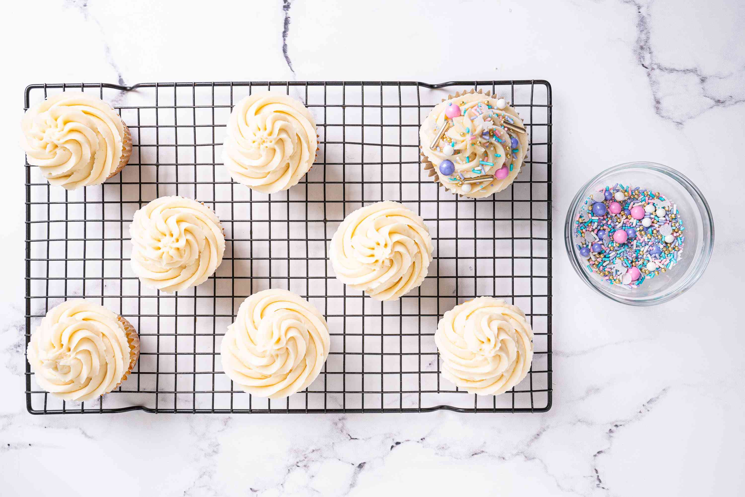 Adding sprinkles to the frosted cupcakes