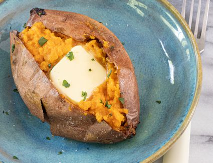 air fryer sweet potato with butter and cilantro garnish