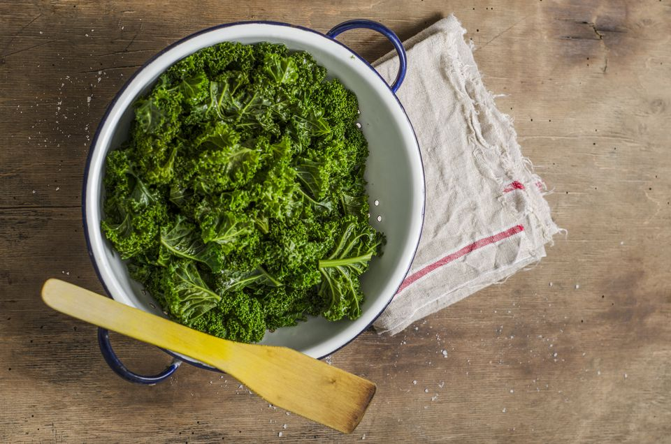 Steamed green cabbage in colander, wooden spoon