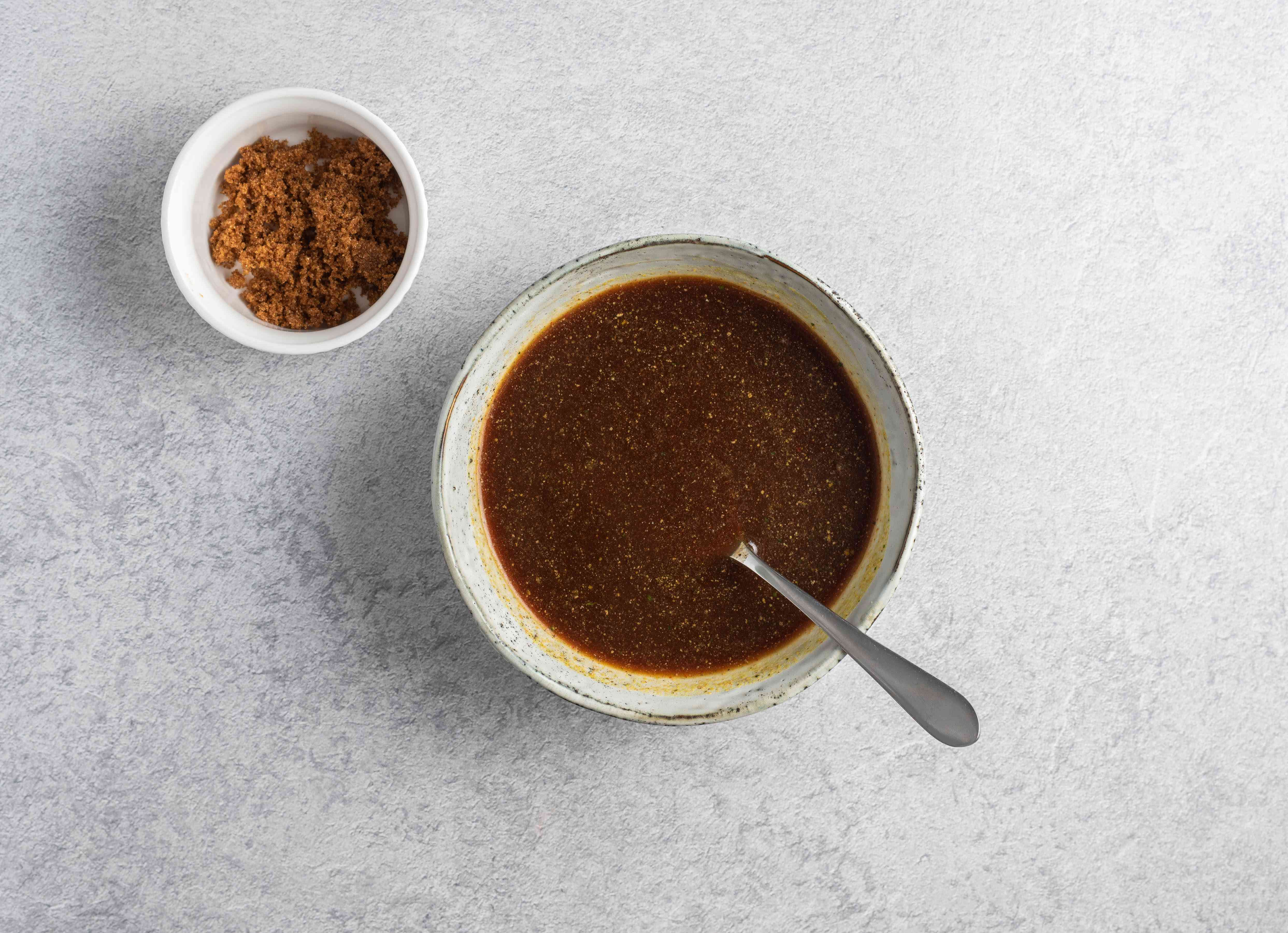 Adding more brown sugar to the sauce using a spoon