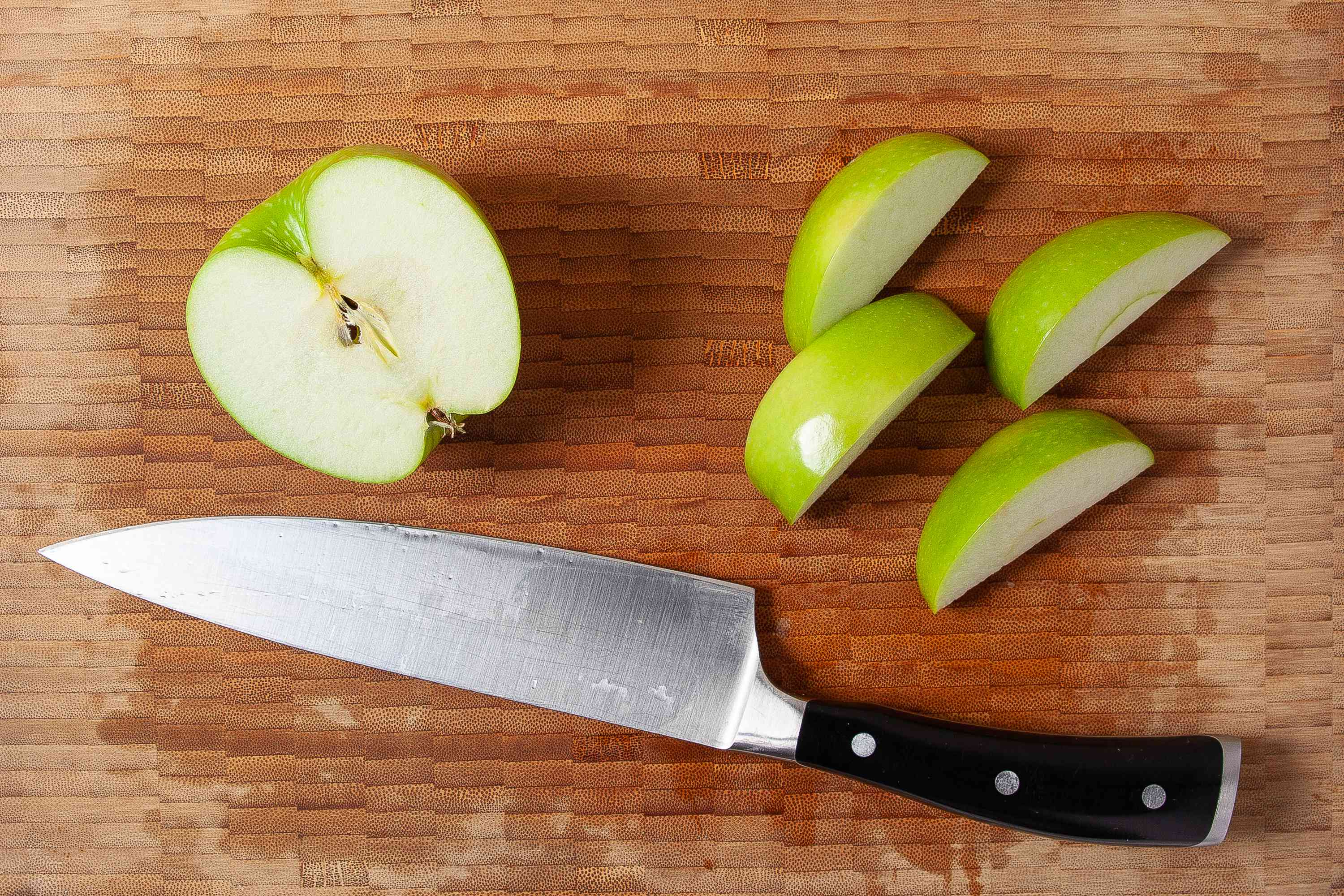 Granny smith apple cut into eight wedges on a wooden cutting board