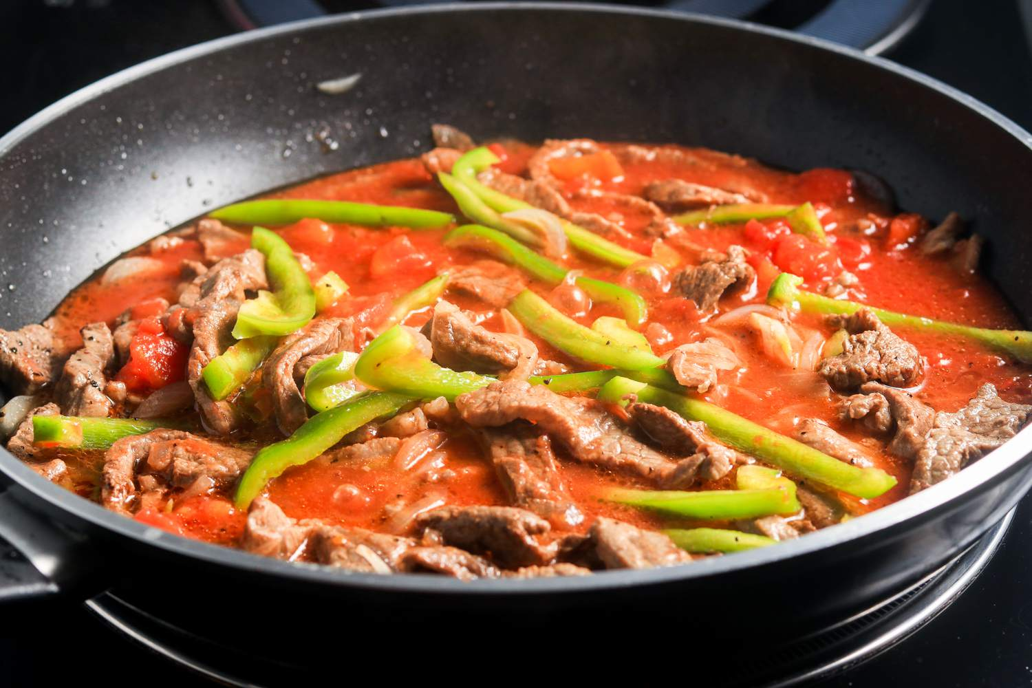 Add stewed tomatoes and bell pepper to steak mixture in skillet