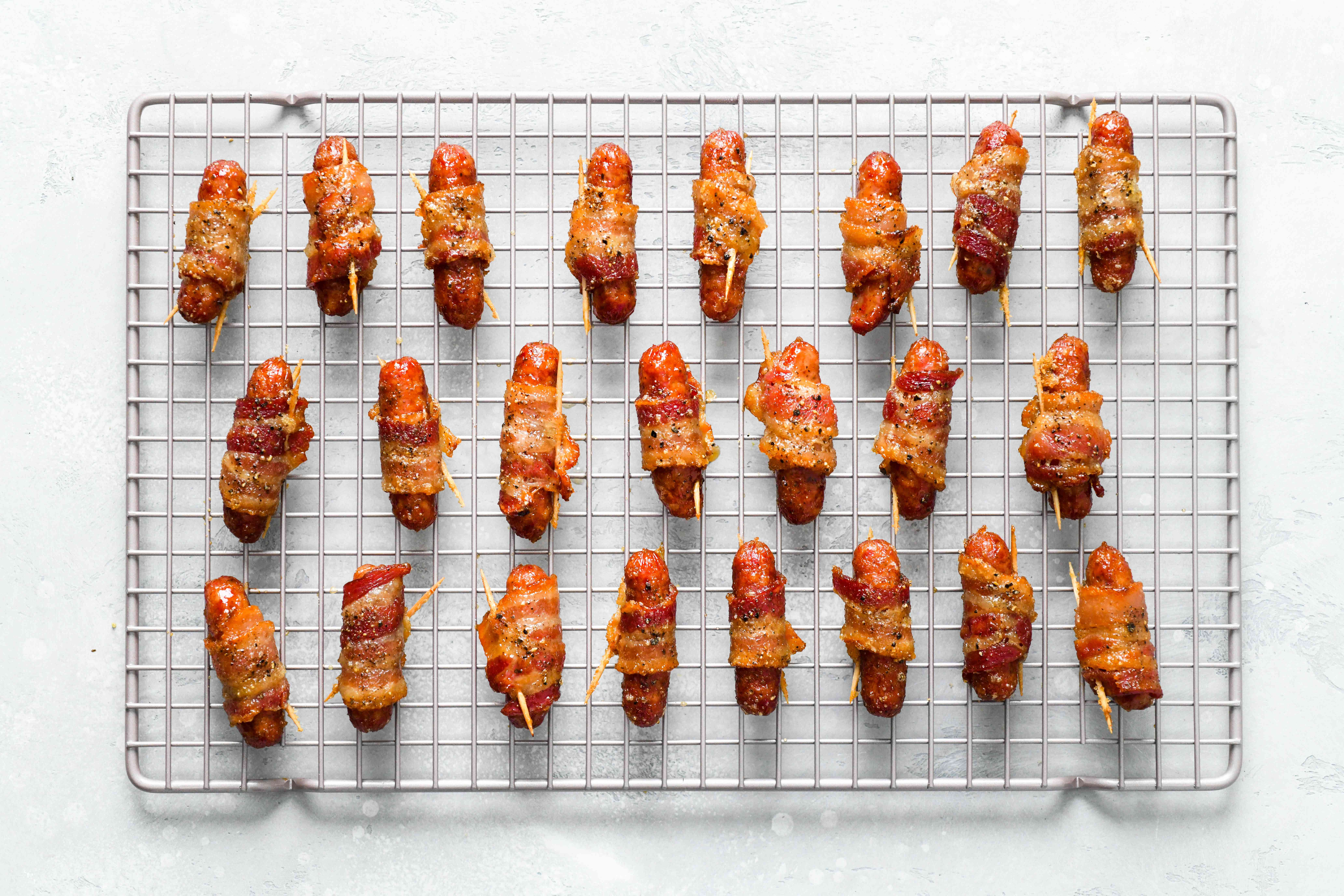 Bacon-wrapped sausages cooling on a wire rack
