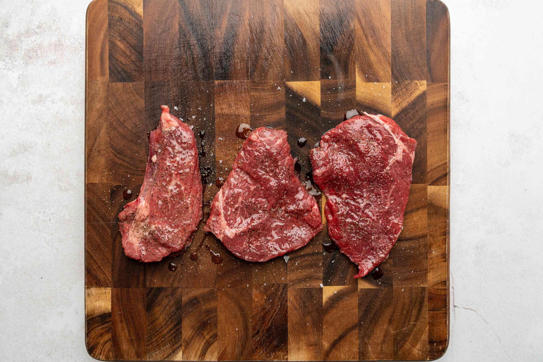 seasoned steaks on a cutting board