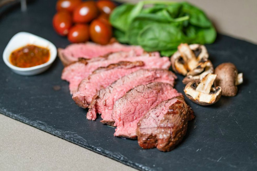 Simple grilled tri-tip steak on slate with mushrooms, grape tomatoes, and lettuce