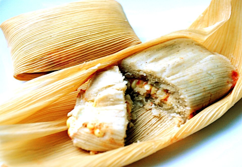 An open corn husk with a split tamale