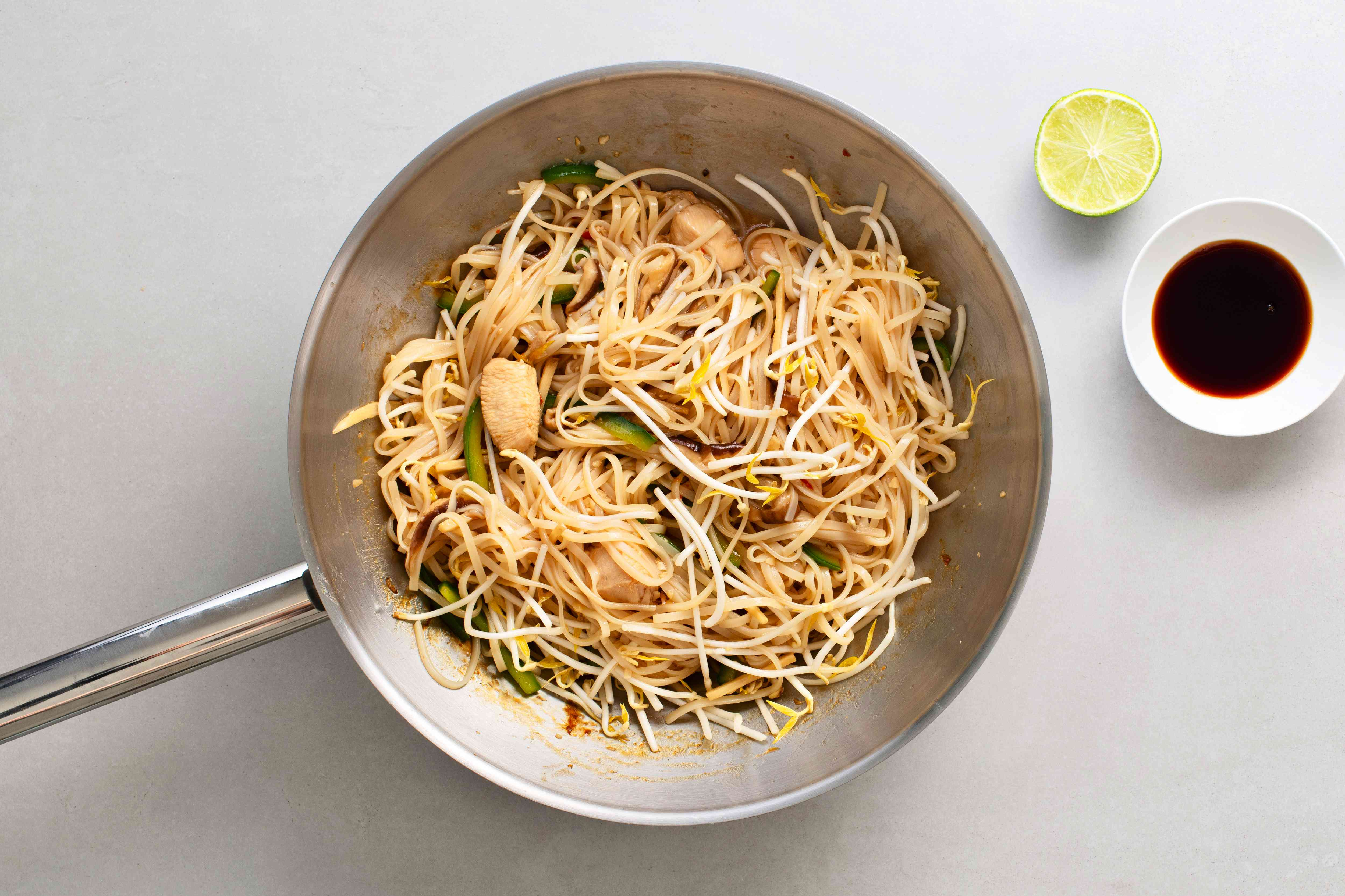 stir fry cooking in a pan with fish sauce and lime juice