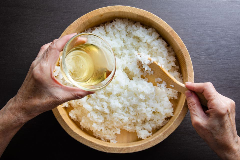 Rice wine being poured into bowl of rice for sushi