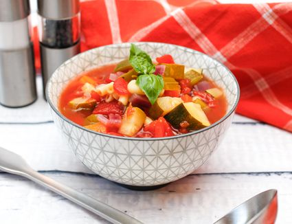 Bowl of vegetarian minestrone soup on a white table