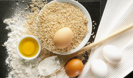 High angle view of brown rice with flour and eggs