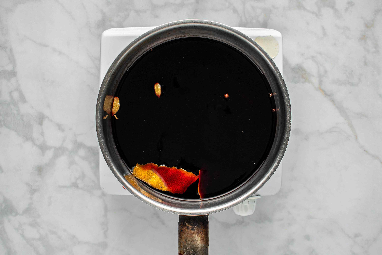 Combine wine, sugar, cloves, cinnamon sticks, cardamom, and peeled orange zest in a large saucepan