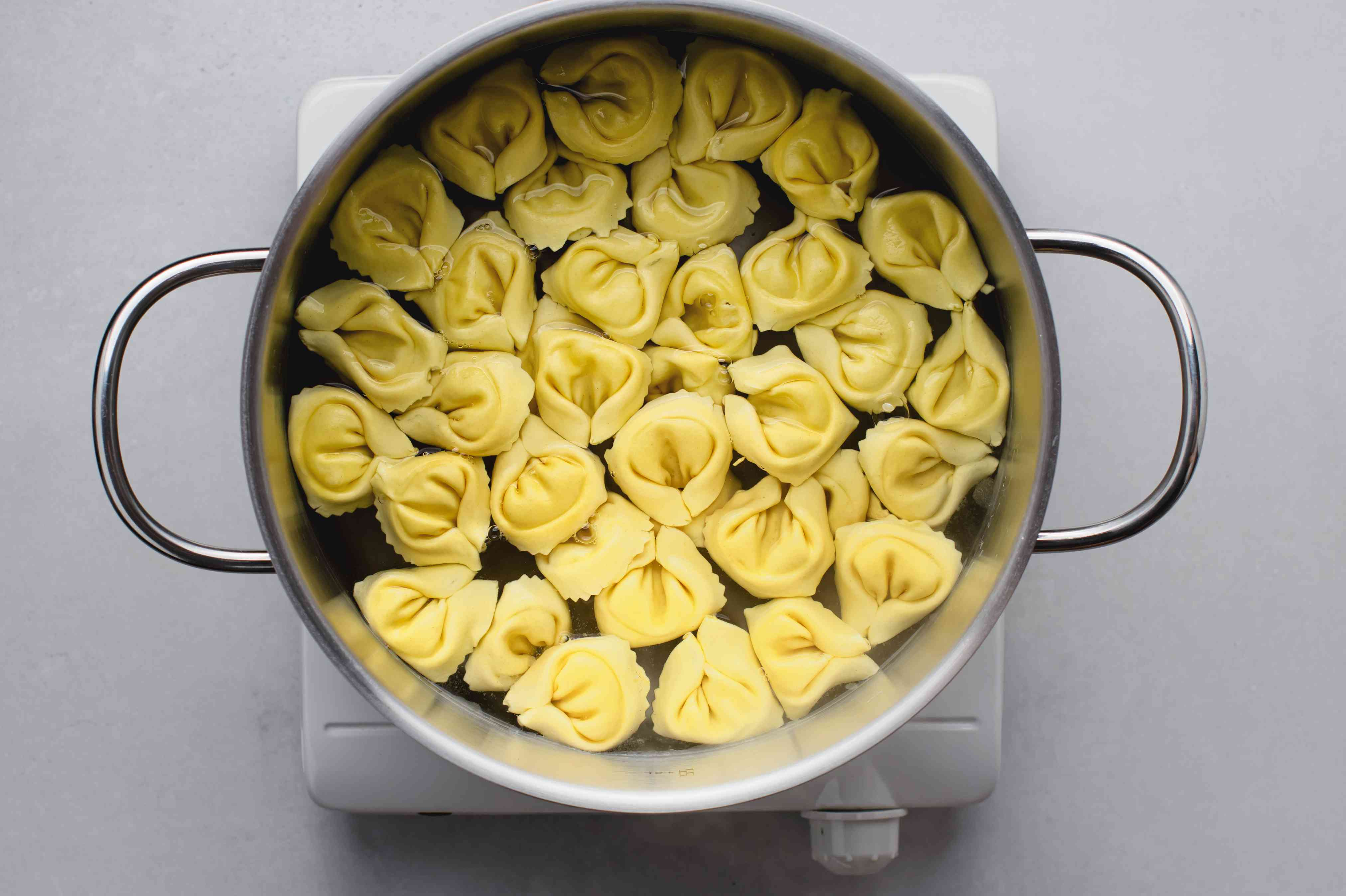 Cook the tortellini in a pot with water