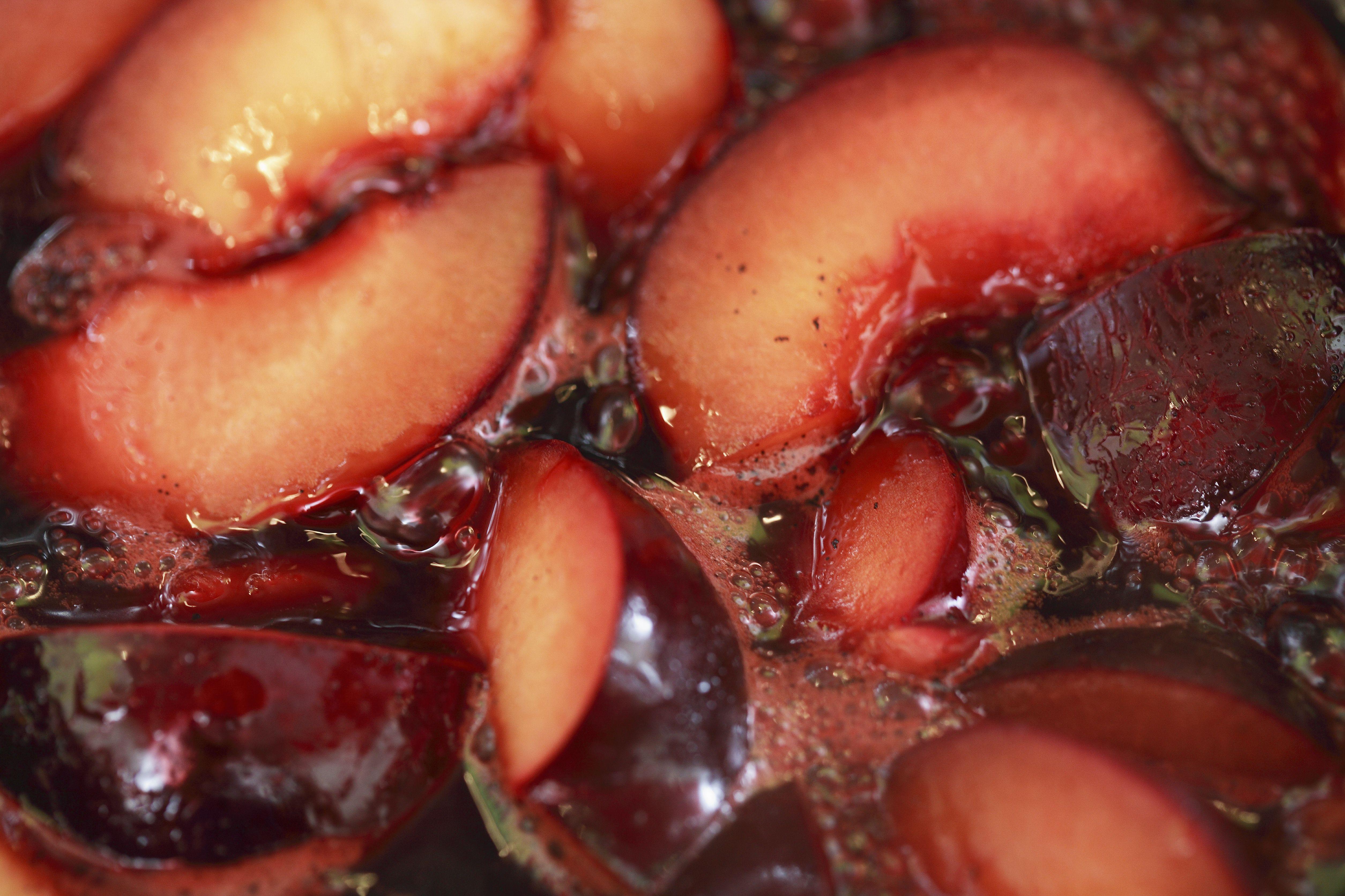 Sliced plums simmering in plum juice