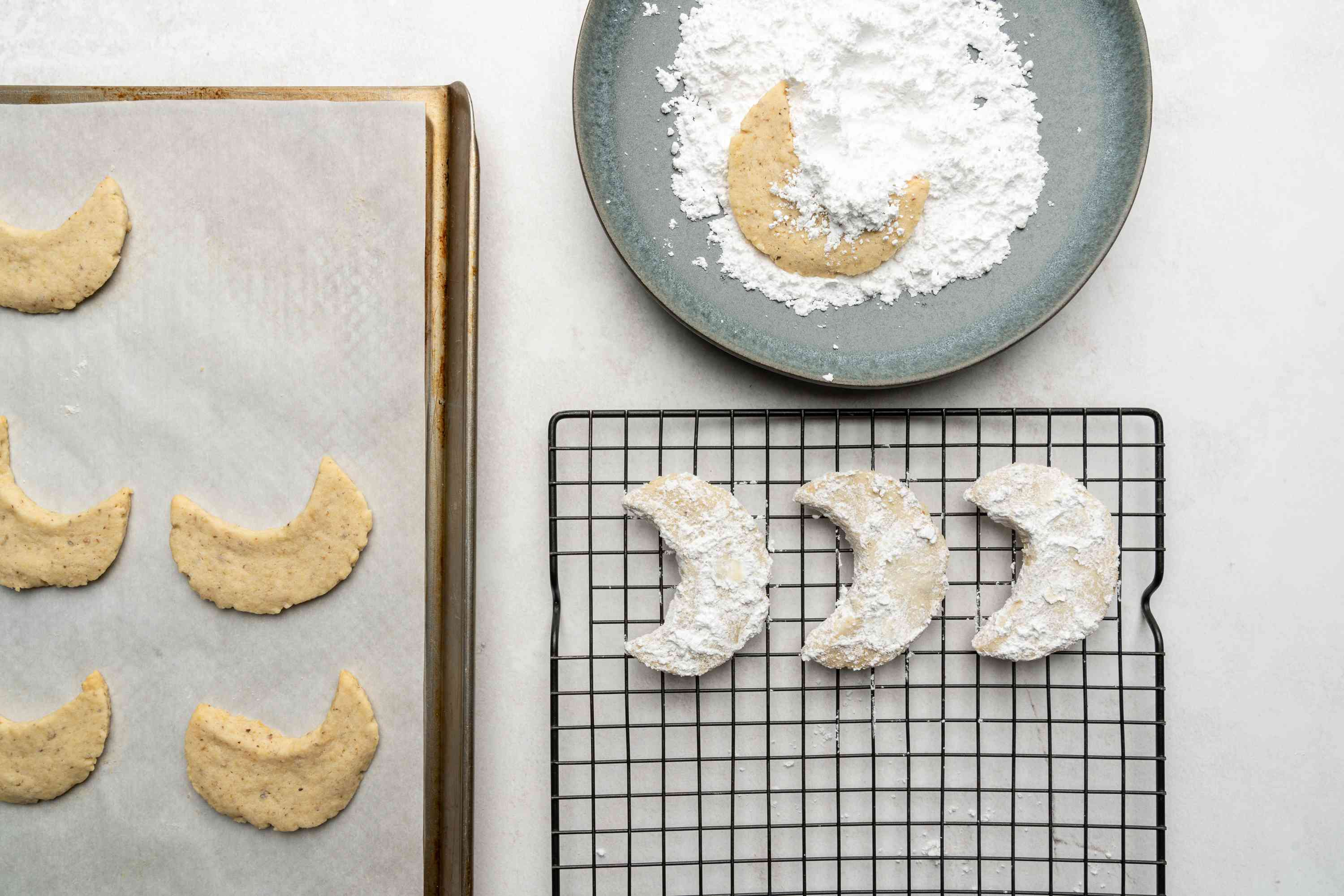 Walnut Crescent Cookies in a bowl with powdered sugar, on a cooling rack