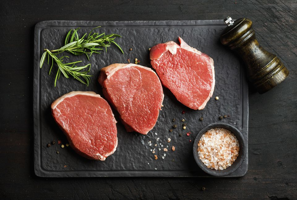 Raw beef Eye Round steaks with spices and rosemary on black slate stone board over dark wooden background