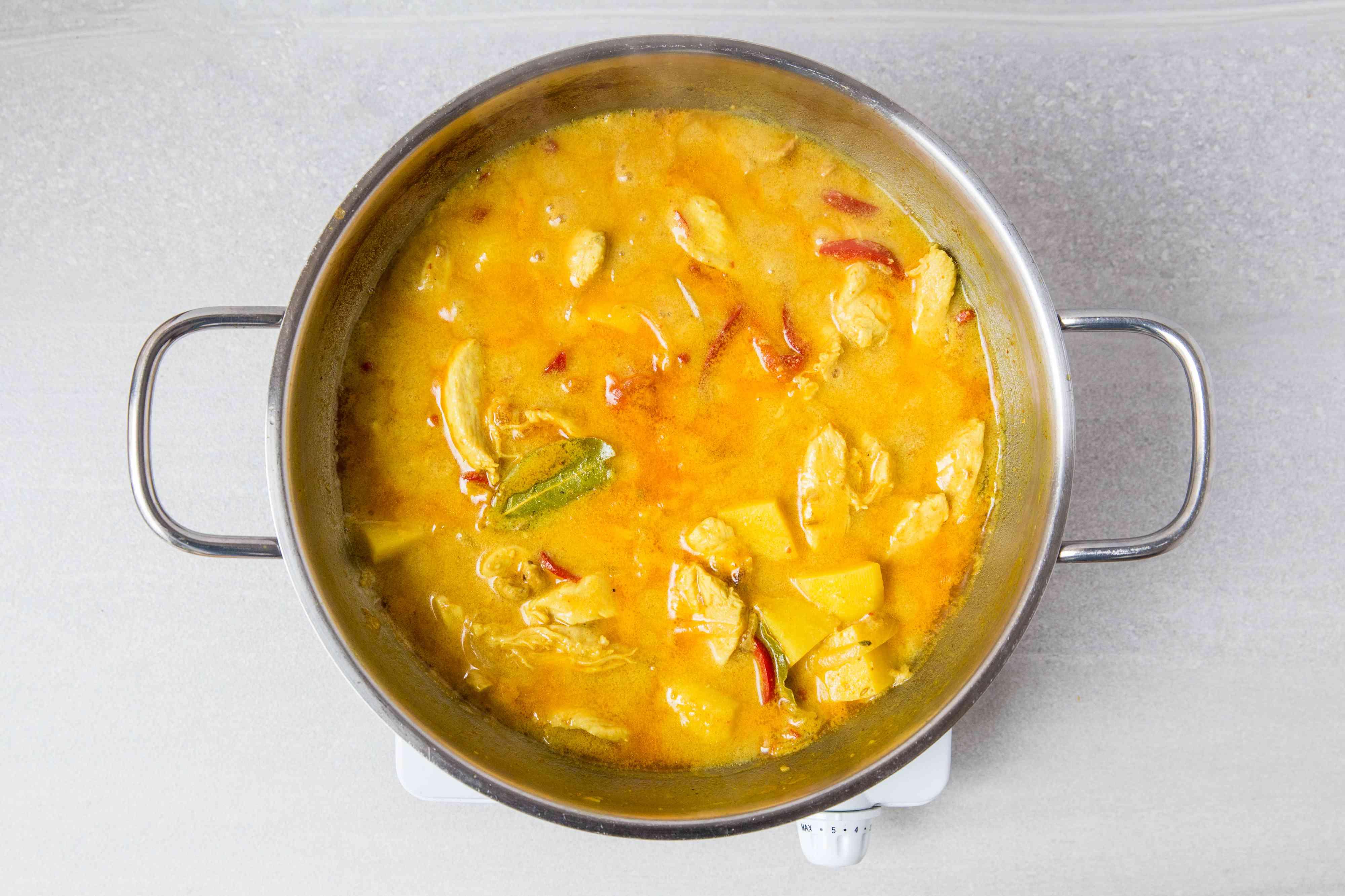 A pot of Thai massaman chicken curry simmering